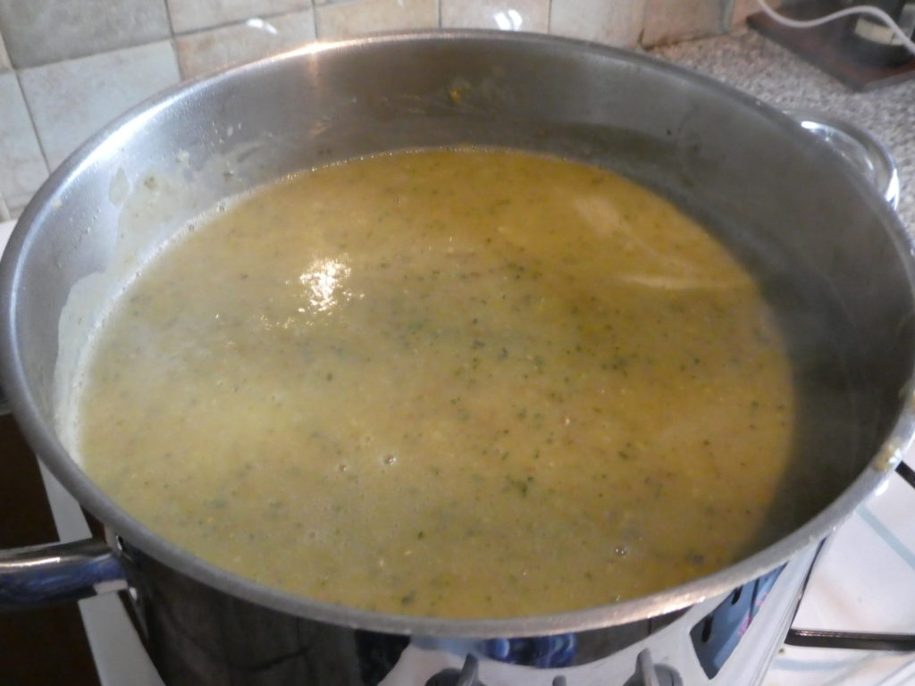 A large steel pot with greeny coloured Courgette Soup