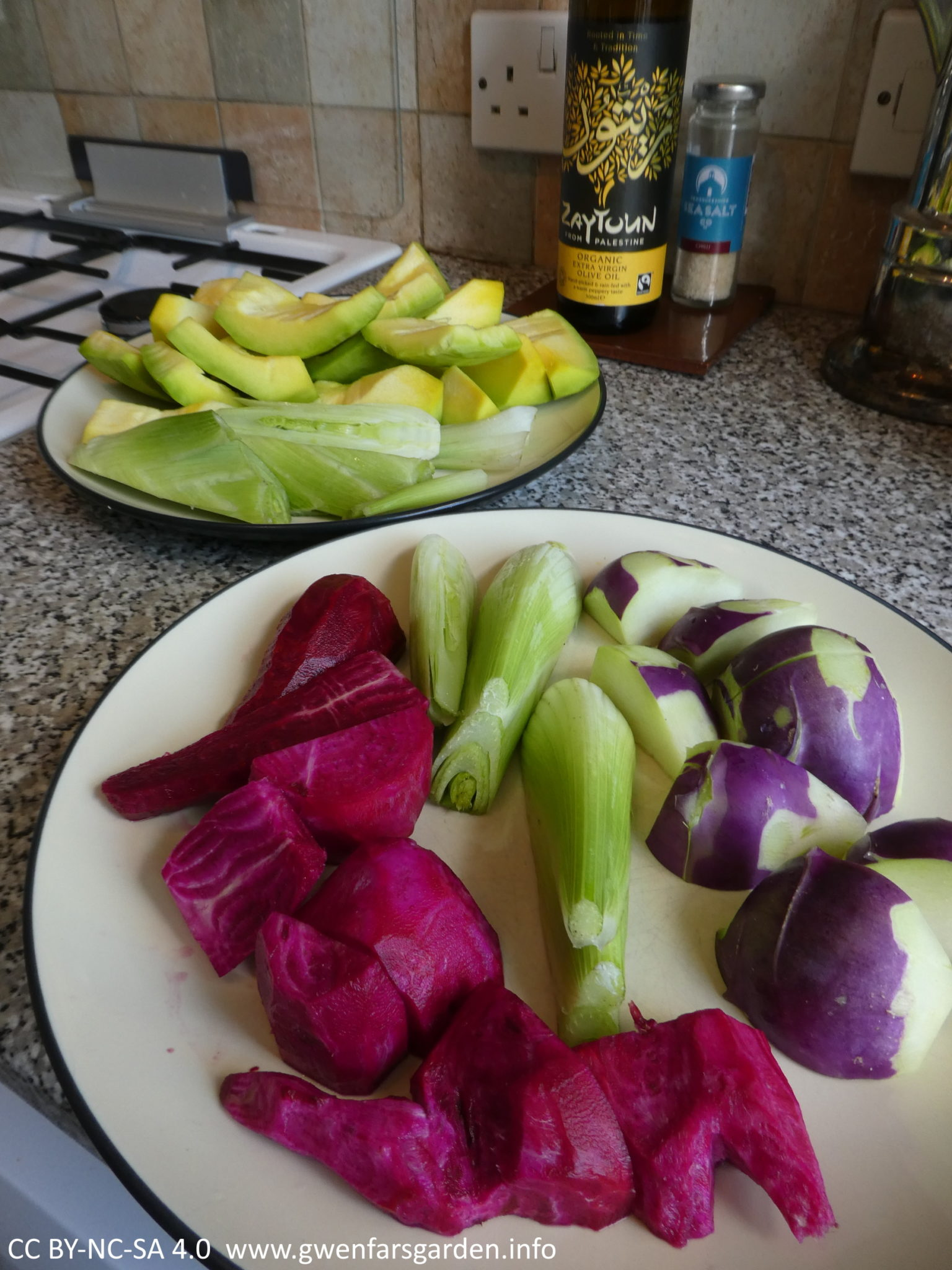 Two plates of veggies peeled and cut up, from the garden. The top one has the small yellow Sibley squash cut up, plus some fennel bulbs. The bottom one has purple kohlrabi and red-magenta beetroot.