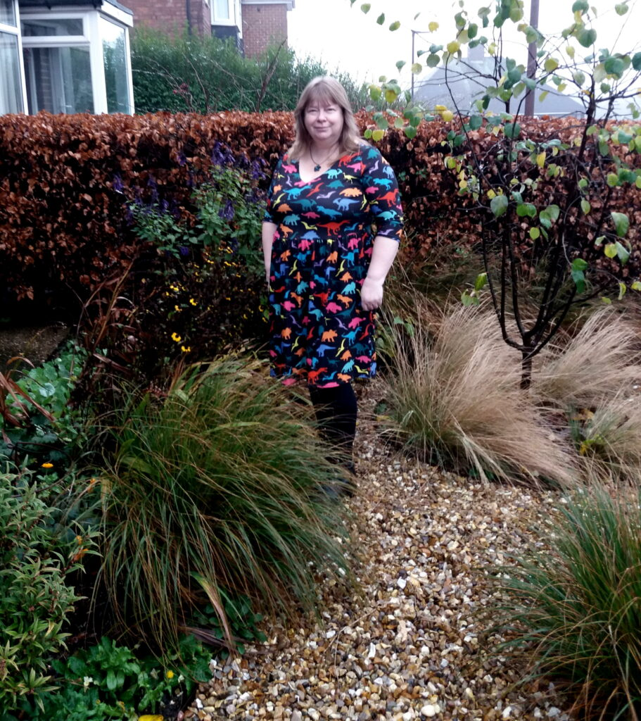 A white woman with blonde hair standing on the gravel path of her front garden. You can see grasses, perennials and a Quince tree, with a beech hedge behind her.