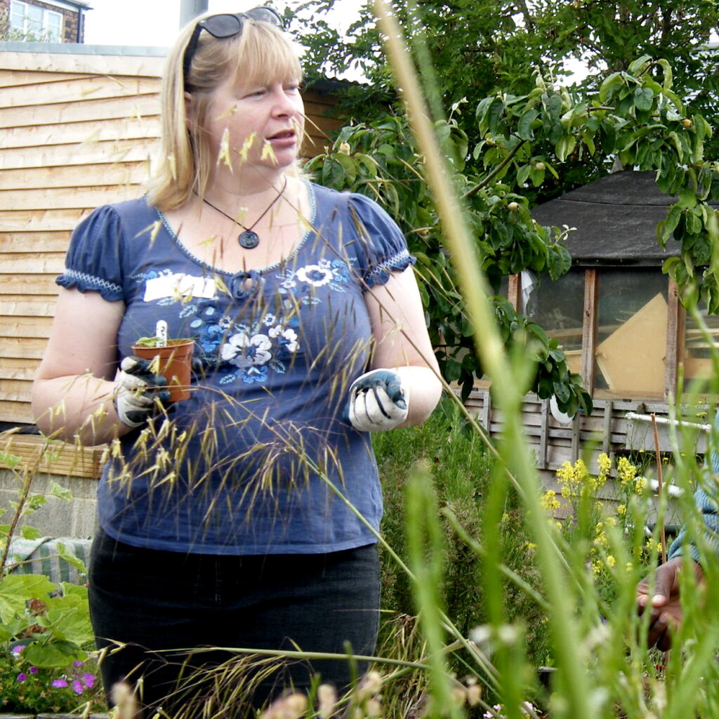 A white blonde woman standing in the community garden, wearing gardening gloves and holding a small pot with a young plant in it. She is looking to the right, and is talking about potting on or planting out young plants.