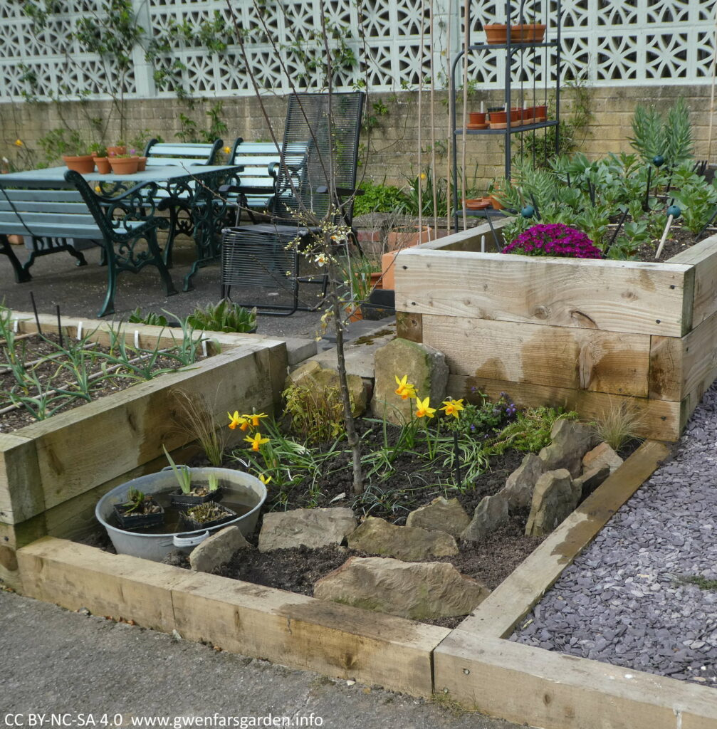 An overview of the scree bed all filled in and several large flat stones standing up and plants will be grown inbetween these.