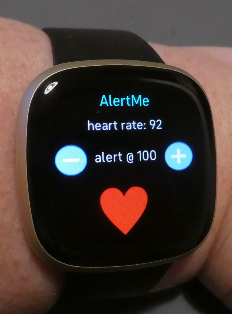 This is the AlertMe app on my Fitbit. Again it has a black background screen, with AlertMe in turquoise, then on the next line: heart rate: 92 in white. In the middle in white is: alert @ 100 with a minus and plus sign on each side and under this a red heart shape.