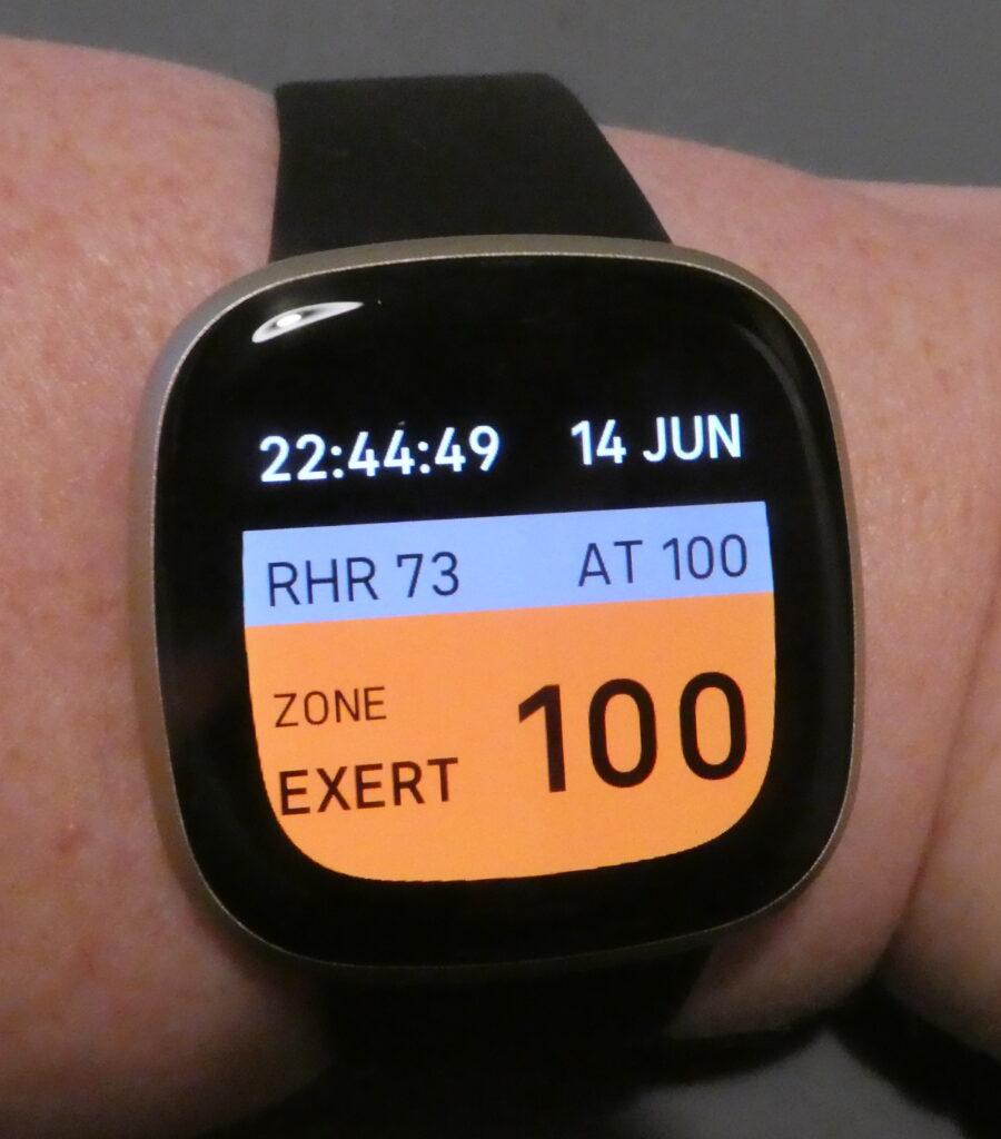 A large watch screen on a white wrist. It has a black background, with the time and date in white at the top. In the middle, in a grey panel it has the RHR, resting heart rate, and the AT 100, the bpm threshold I set. Then there is an orange panel that says Zone Exert on the left and the number 100 on the right. I've just reached my anaerobic threshold.