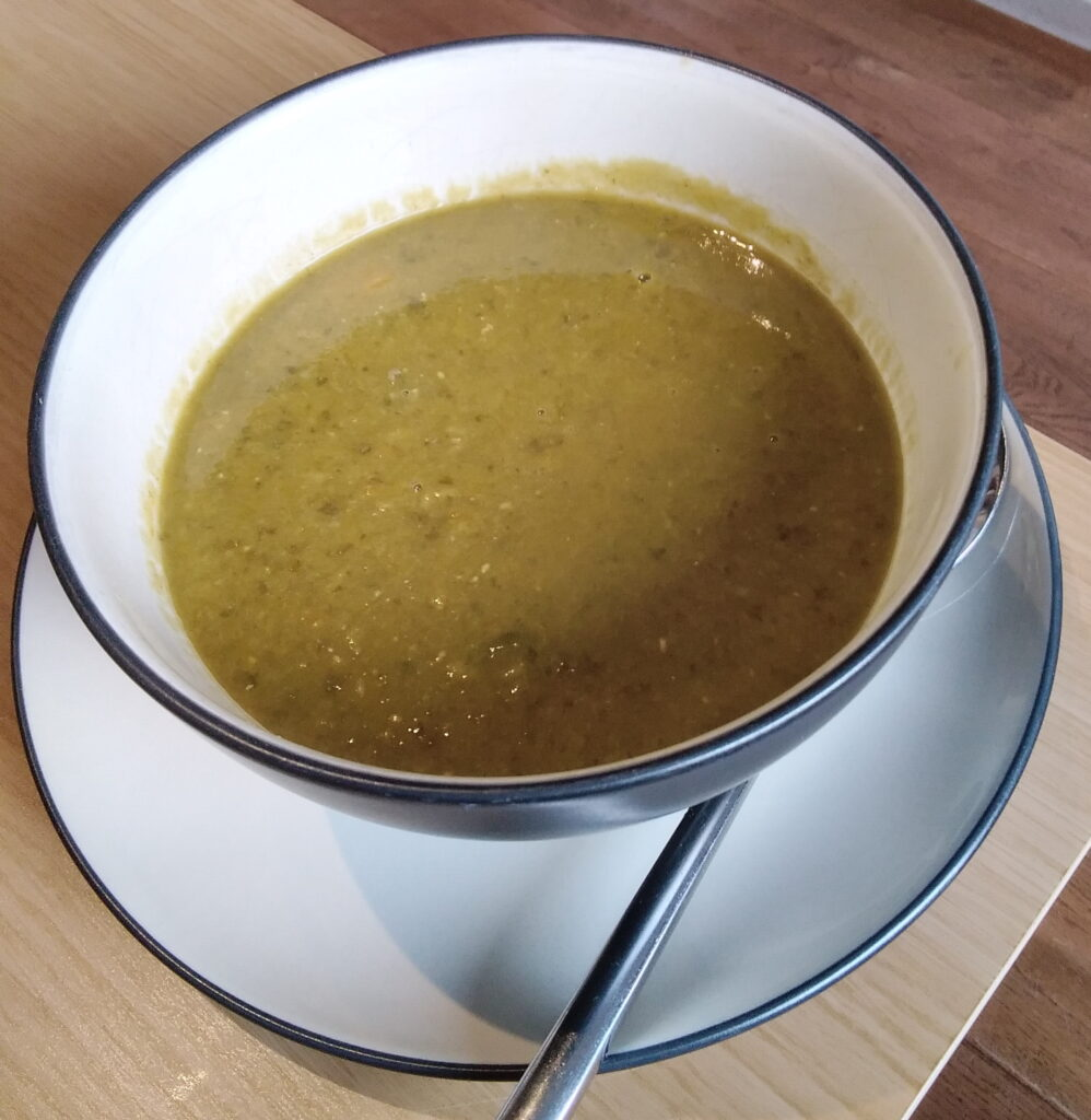 A soup bowl with a green creamy sorrel and lentil soup in it.